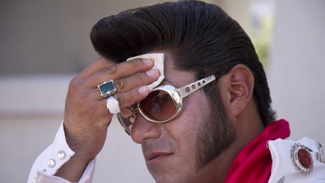 Elvis impersonator Cristian Morales wipes sweat from his brow while standing out on The Strip posing for photos with tourists