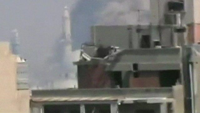 Still from unverified amateur footage purportedly shows smoke rising from a thirteenth century mosque hit by shells in Homs