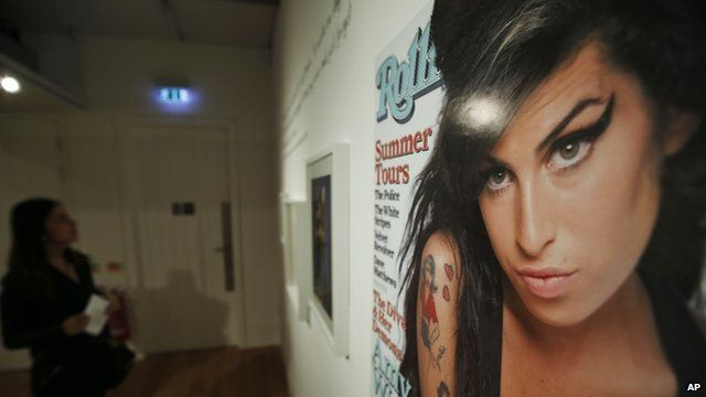 Visitor looking at Amy Winehouse memorabilia, including Rolling Stone cover