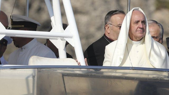 """A gust of wind lifts up Pope Francis"""" mantle as he stands onboard a boat at Lampedusa Island, southern Italy, July 8, 2013"""