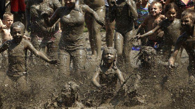 Children run into the mud in Westland, Mich., Tuesday, July 9, 2013