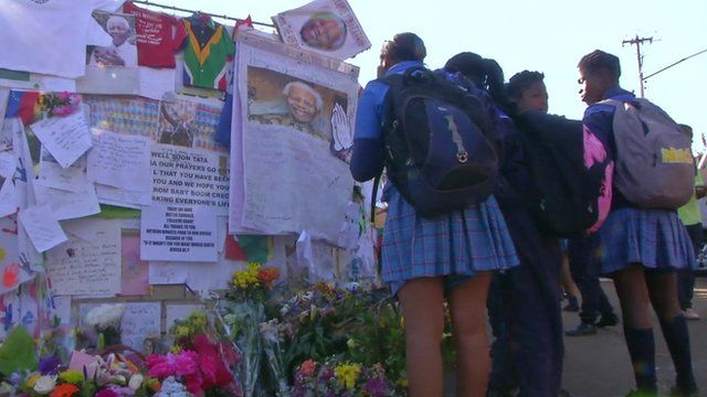 Schoolgirls look at tributes to Nelson Mandela