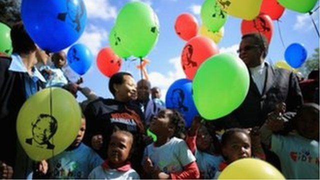 Children with Nelson Mandela balloons outside the Pretoria hospital where he is being treated
