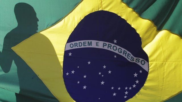 The shadow of a demonstrator is cast on a Brazilian flag