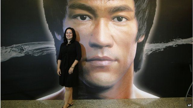 "Shannon Lee, daughter of the late Kung Fu star Bruce Lee, poses in front of a promotional poster for Lee""s memorial exhibition"