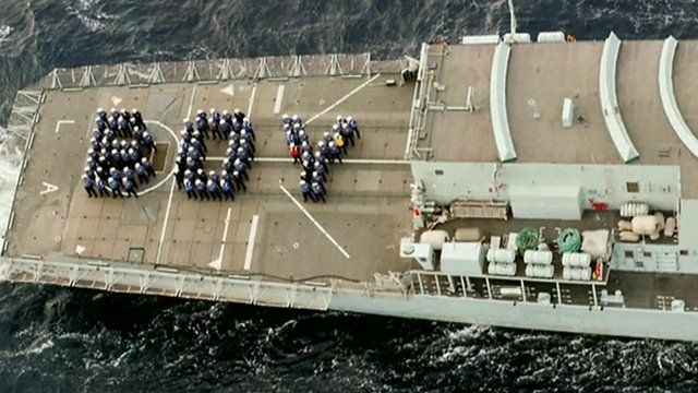 Service personnel spell out the word 'boy' on deck