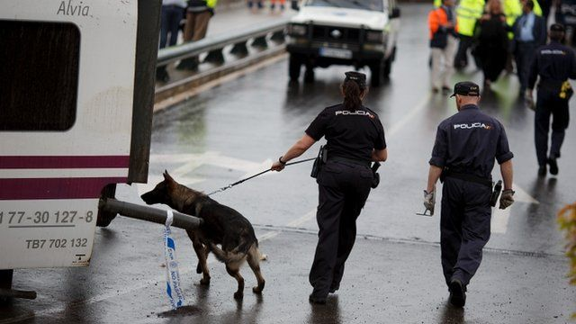 A police dog checks the area before Prime Minister Mariano Rajoy arrives at a the scene of a train crash that killed at least 78 people