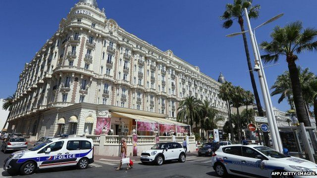 Police cars are parked outside the Carlton Hotel
