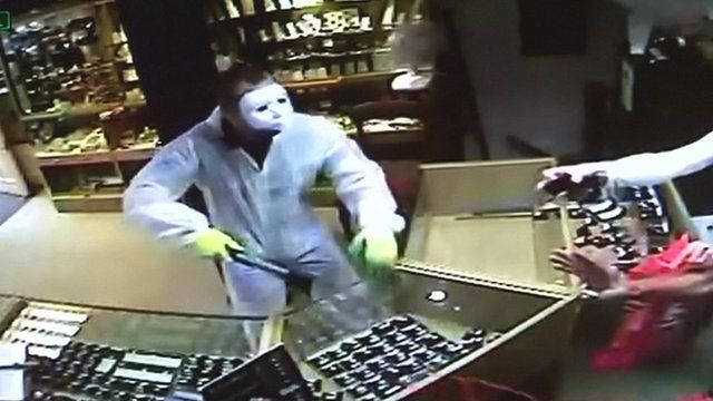 Masked robber with axe in shop