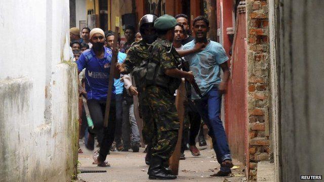 Special Task Force soldiers block Muslim men outside vandalised mosque