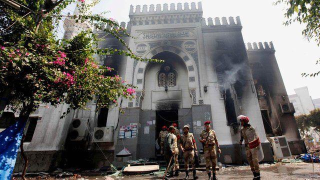 Members of the military police stand outside the burnt Rabaa al-Adawiya mosque