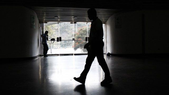 A security guard walks past an exit door as he waits for the power to return after a blackout during the FIBA Americas Championship basketball game between Paraguay and Dominican Republic in Caracas