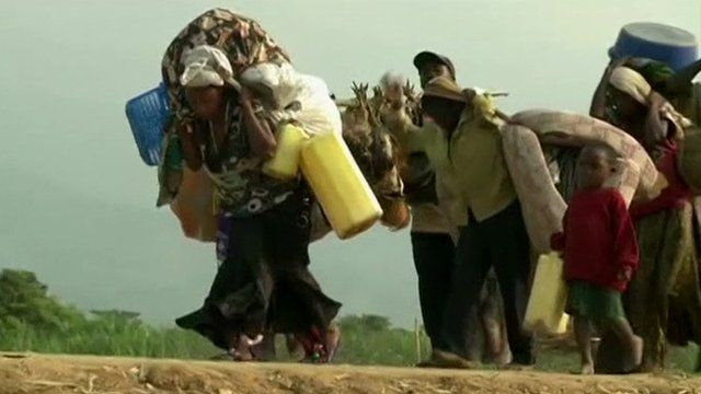 DRC refugees walking on a dusty road, carrying their belongings with them.