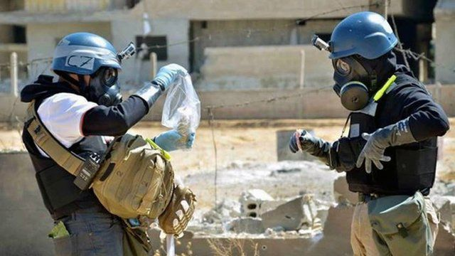 Members of the UN investigation team take samples from sand near a part of a missile that is likely to be one of the chemical rockets according to activists