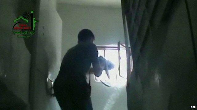A man firing a gun through a window