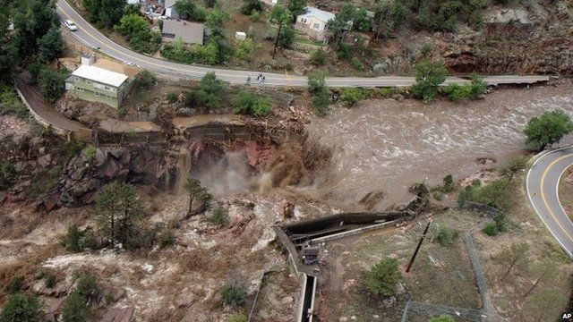This aerial photo shows a raging waterfall destroying a bridge along Highway 34 toward Estes Park, Colo