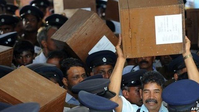 Sri Lankan election workers carry ballot boxes before boarding buses as they prepare to go to polling centres in Jaffna (20 September 2013)