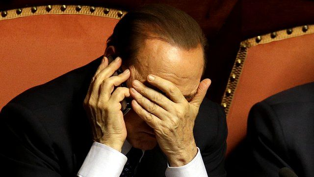 Silvio Berlusconi covers his face as he speaks on a mobile phone after delivering his speech at the Senate in Rome