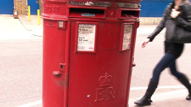 Woman walks behind post box
