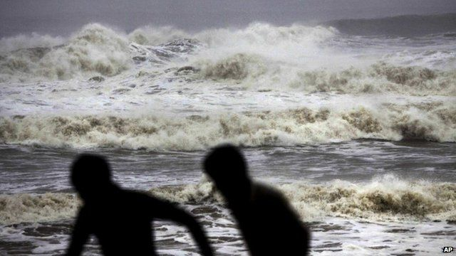 Two people run from huge waves on Gopalpur beach in Ganjam district
