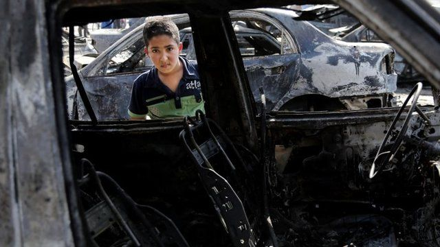 "A boy inspects a destroyed car after a car bomb attack hit the Sha""ab neighbourhood of Baghdad"
