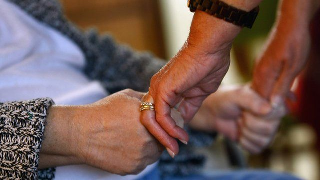 Carer holds patient's hand