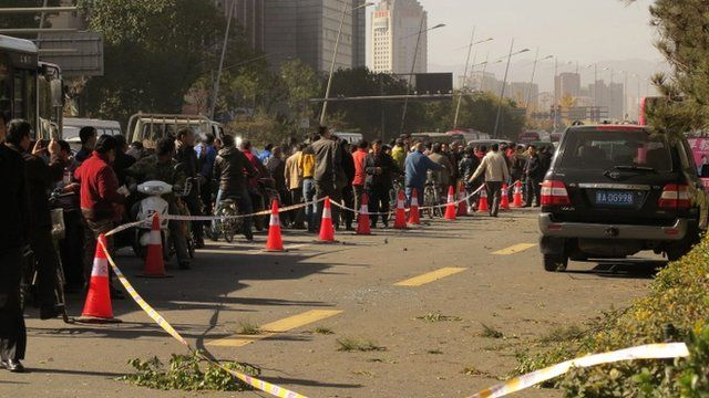 People stand on a street after an explosion outside a provincial headquarters