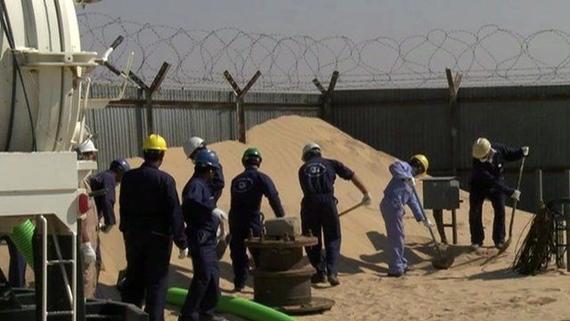 Workers clearing sand
