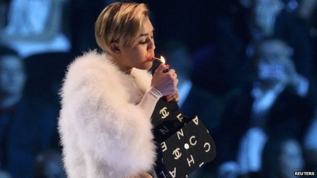 Miley Cyrus lights a cigarette on stage during the 2013 MTV Europe Music Awards