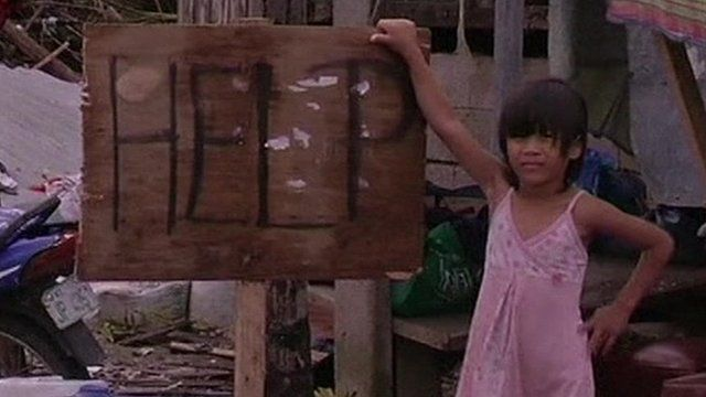 "A young girl stands beside a sign reading ""Help"""