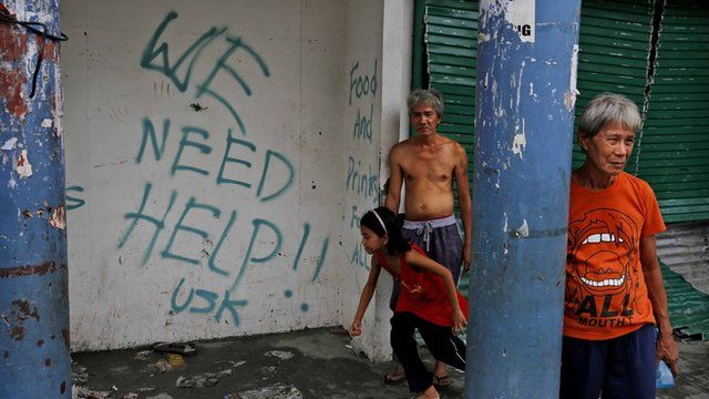 Residents in Tacloban stand next to graffiti requesting aid in the aftermath of Typhoon Haiyan