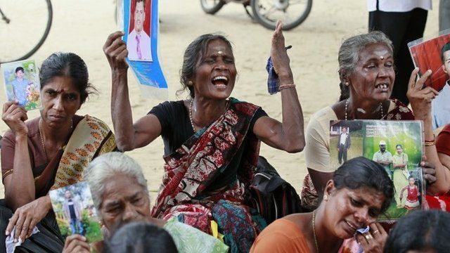 Sri Lankan ethnic Tamil women cry holding portraits of their missing relatives during a protest in Jaffna, Sri Lanka, Friday, Nov. 15, 2013.