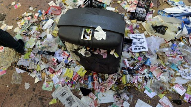 A street bin surrounded by rubbish is seen in the centre of Madrid on November 14, 2013 during an open-ended strike by street-sweepers against layoffs and salary cuts