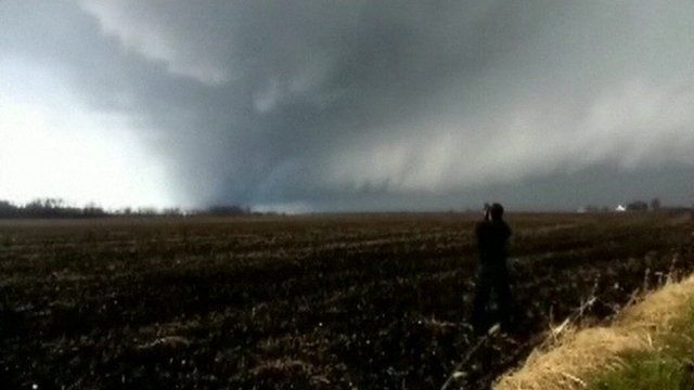 Man in field photographing tornado
