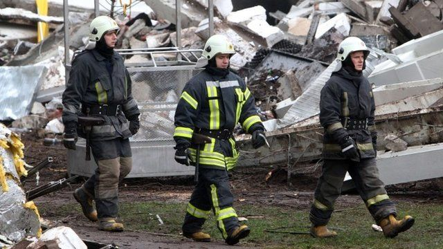 Rescuers walk at the site of the Maxima supermarket in Riga on November 23, 2013, after the roof of the building caved in on shoppers on November 21