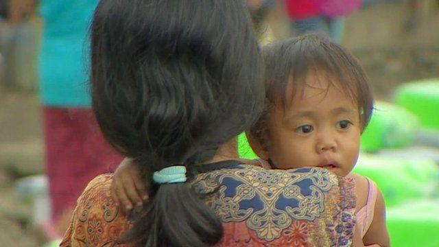 Mother carries child amidst typhoon Haiyan debris