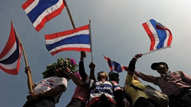 Thai anti-government protesters wave national flags as they stand on a barricade outside Government House during a rally in Bangkok on December 9, 2013