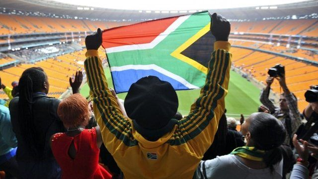 A man holds a South African flag at the Memorial Service for former South African President Nelson Mandela