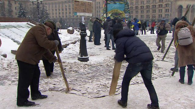 People try to break ice on the ground of Kiev's Independence Square