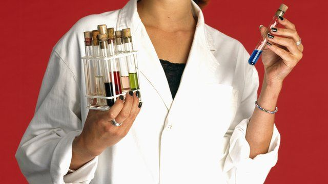A woman in a lab coat with test tubes