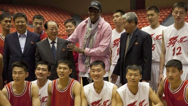 Former NBA basketball star Dennis Rodman poses for pictures with North Korean basketball players and government officials during a practice session in Pyongyang, North Korea