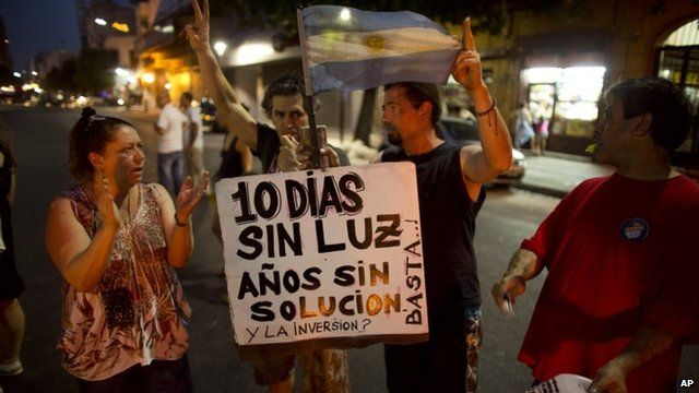 Four protesters with Argentinean flag and sign in Spanish
