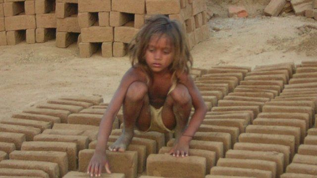 Child sat on bricks