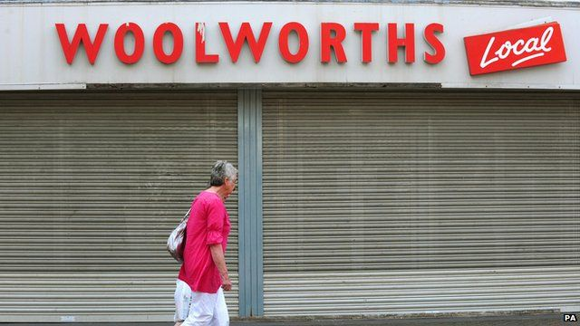 Woman walks past Woolworths shop front