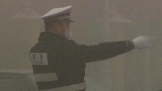 Beijing traffic officer in smog