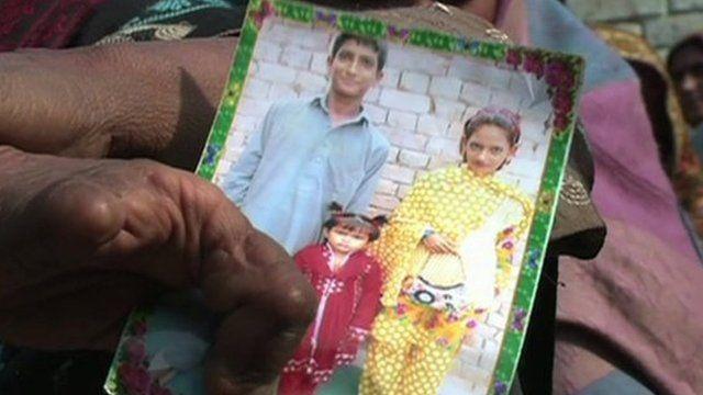 Pakistani mother holding photograph of children