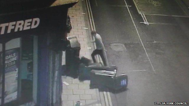 CCTV still shows man knocking over wheelie bins on a York street