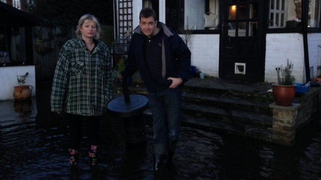 Local residents Deborah Carter and Gavin Segar stand in floodwater