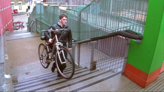Man carrying cycle up steps