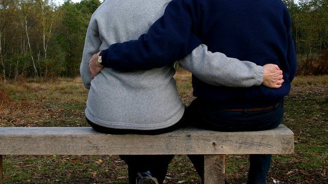 Couple embrace on park bench